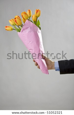 Man's hand holding a bouquet of orange tulips