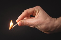 Man's hand holding a burning match. Photo on a black background