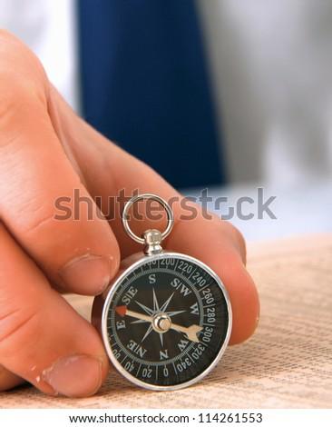 Man's hand holding a compass.