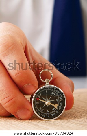 Man's hand holding a compass.