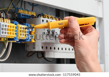 Man's hand holding a detector and switchboard