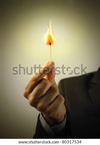 Man's hand holding a match