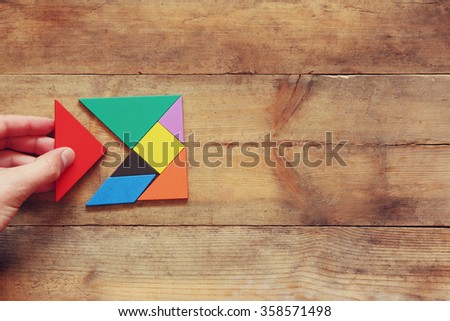 man\'s hand holding a missing piece in a square tangram puzzle, over wooden table.