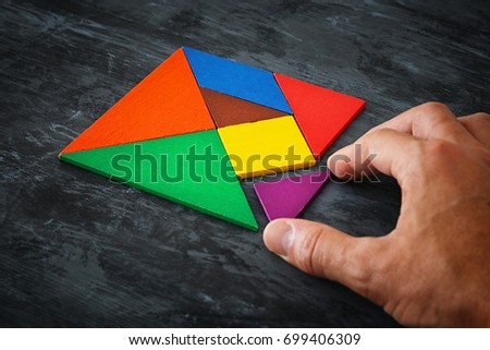 man's hand holding a missing piece in a square tangram puzzle, over wooden table. #699406309