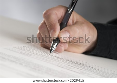 man's hand holding a pen writing his signature