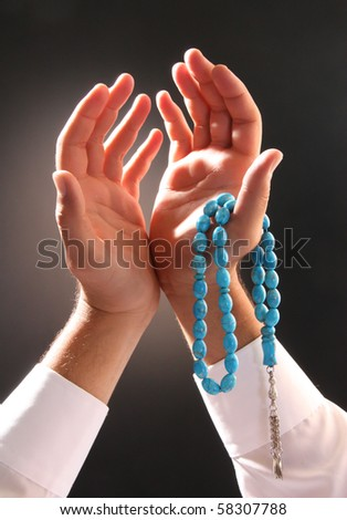 man's hand holding a rosary in a pose of praying and asking