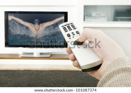 Man's hand holding a tv remote control, pressing a button while pointing at a flat screen tv.