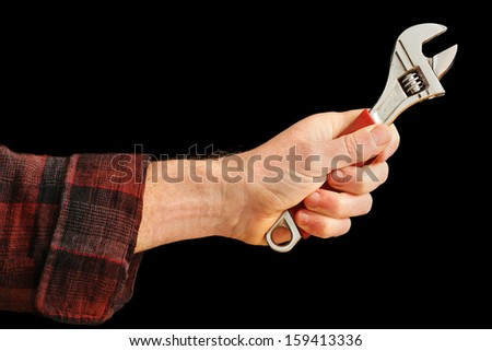 Man's Hand holding an Adjustable Spanner isolated on black