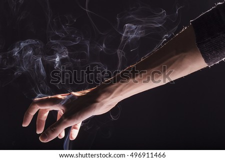 Man's hand holding and playing with smoke, dramatic and dark, black background. Smoke bender, elemental control #496911466