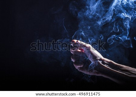 Man's hand holding and playing with smoke, dramatic and dark, black background. Smoke bender, elemental control #496911475
