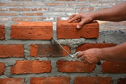 Man's hand holding brick onto cement and the other hand holding a trowel as to make a brick wall