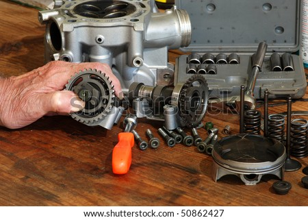 Man's hand holding camshaft gear with disassembled four-stroke engine of motocross bike scattered on old wooden workbench.  Socket set and nut driver included.
