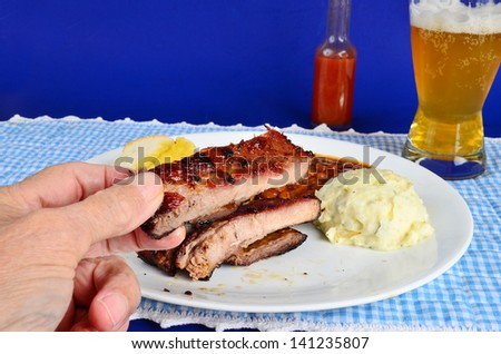 Man's hand holding charbroiled rib with baked beans and potato salad on white plate in background.  Served with beer and buttered garlic bread against blue background.