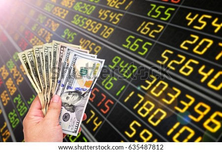 Man's hand holding Dollar (USD) banknotes on stock market background. #635487812