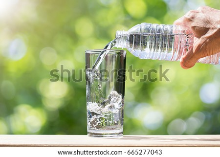 Man's hand holding drinking water bottle water and pouring water into glass on wooden tabletop on blurred green bokeh background with soft sunlight