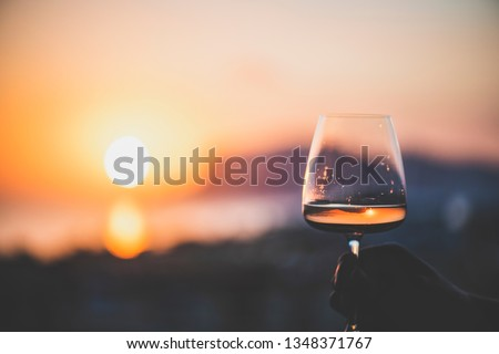 Photo of  Man's hand holding glass of rose wine and with sea and beautiful sunset at background, close-up, horizontal composition. Summer evening relaxed mood concept