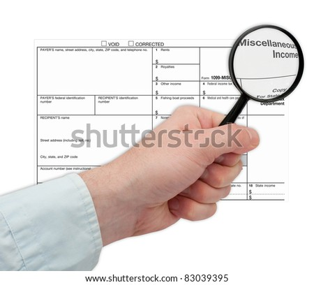 Man's Hand Holding Magnifying Glass over 1099 Tax Form