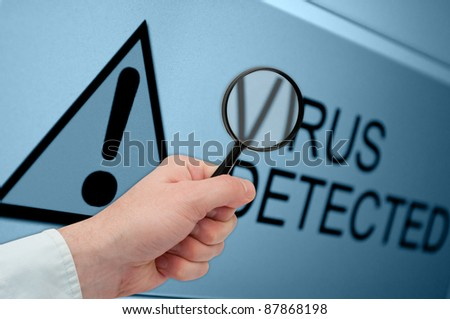 Man's Hand Holding Magnifying Glass over Virus Detected Sign on Monitor