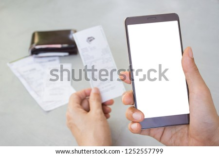 Man's hand holding mobile phone with white screen and holding bill or slip with blurred leather wallet and utility bills on gray table background