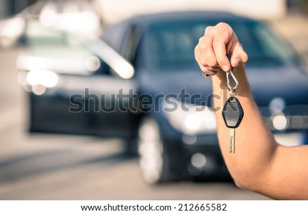 Man\'s hand holding modern car keys ready for rental - Concept of transportation with automobile second hand sale and trade