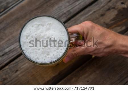 Man's hand holding mug of beer. Octoberfest theme. #719124991