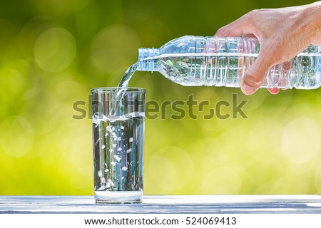 Man\'s hand holding plastic bottle water and pouring water into glass on wooden table on blurred green bokeh background