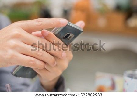 Man's hand holding smart phone or mobile phone in restaurant blur  background