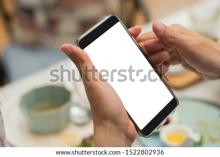 Man's hand holding smart phone or mobile phone with white screen in restaurant blur background
