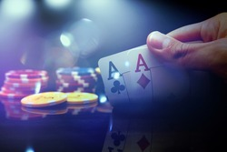 Man's hand holding two aces while playing poker