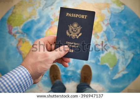 Man\'s hand holding US passport. Map background. Ready for traveling. Open world.