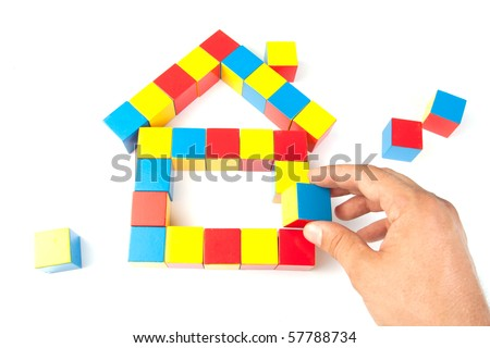 Man's hand holding wooden block. Building a house