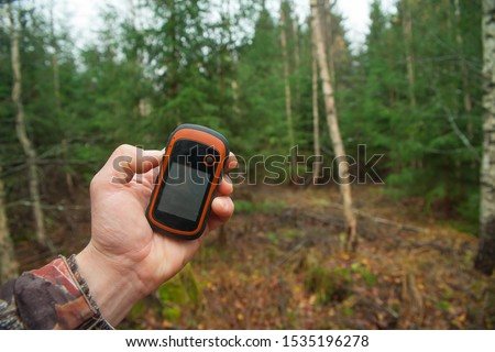 Man's hand holds a GPS navigator. Orientation in the forest using the navigator.