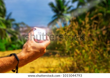 man's hand holds a signaling mirror in the tropics signal light reflection sos sun ask for help