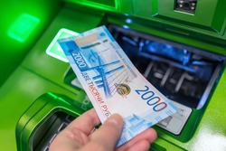 Man's hand holds new Russian banknote of two thousand rubles against background of green cash machine