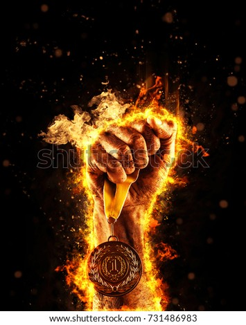 Man's hand in a fire is holding up gold medal on a dark background. Winner in a competition. #731486983
