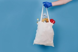 Man's hand in blue disposable protective gloves holding white bag with food donations on blue background. Donation and volunteering concept, mockup and copyspace. Contacless food delivery
