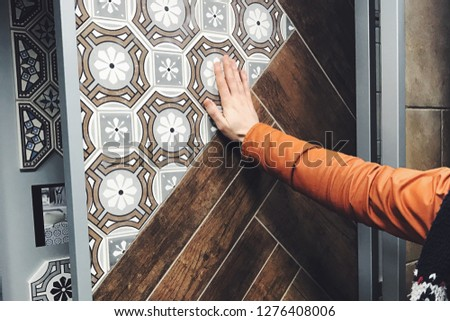 Man's hand in orange vest on beautiful Spanish tiles in a special store for home interior design, reconstruction and architecture