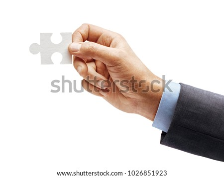 Man's hand in suit holding one puzzle element isolated on white background. Close up. High resolution product