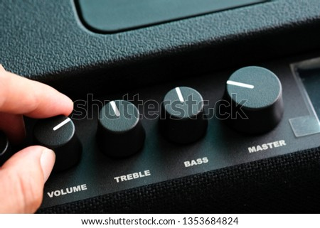 man's hand is adjusting the music volume from the amplifier. #1353684824