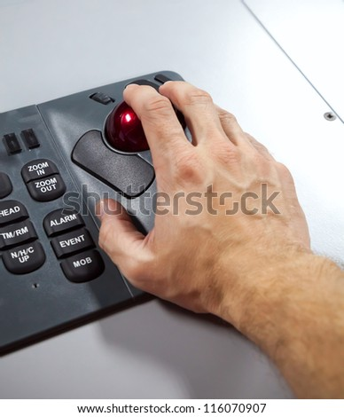 Man's hand on illuminated industrial keyboard with red trackball. Selective focus