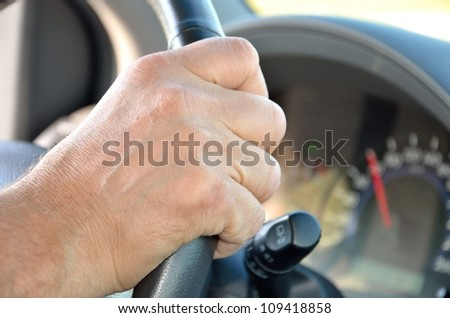 man's hand on the steering wheel of a car