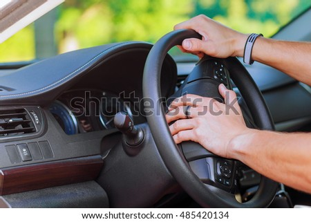 Man's hand on the steering wheel of a car wheel driver car #485420134
