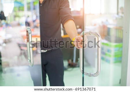 Man's hand open the door with glass reflection background