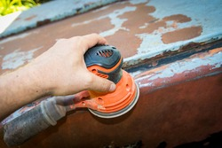 Man's hand operates a disc/orbital sander, to remove paint and rust from metal doors