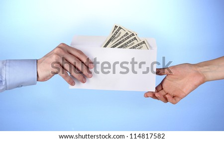 man's hand passes the envelope with dollars on blue background