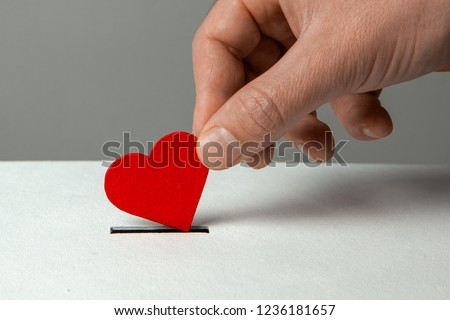 Man's hand places heart in the donation slot. The concept of the donor of blood or human organs, saving lives #1236181657