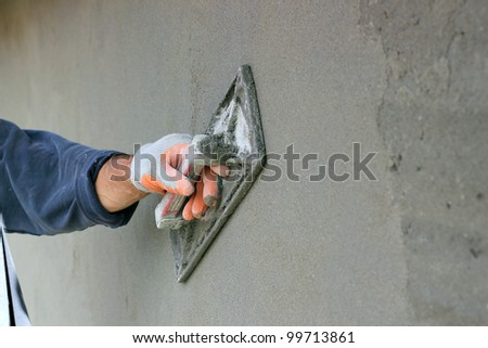 Man's hand plastering a wall with trowel. Construction worker. Masonry tool. Construction industry. Selective focus.