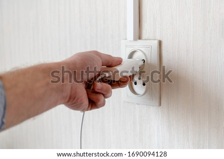 man's hand plugs into a power outlet Photo stock ©
