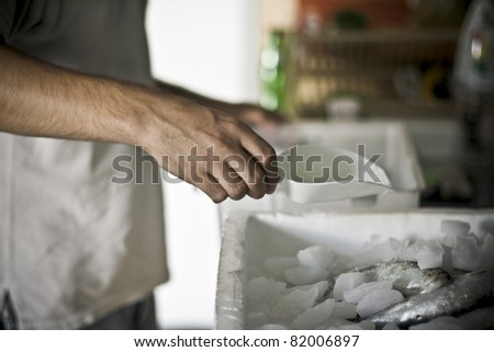 Man\'s hand (position of the hand that can be easily isolated) putting the ice cubes in the box on the fish