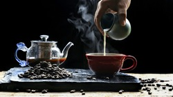 Man's hand pouring milk into red  coffee cup with steam, coffee beans and coffee pot on black slate with wooden table in vintage dark tone style